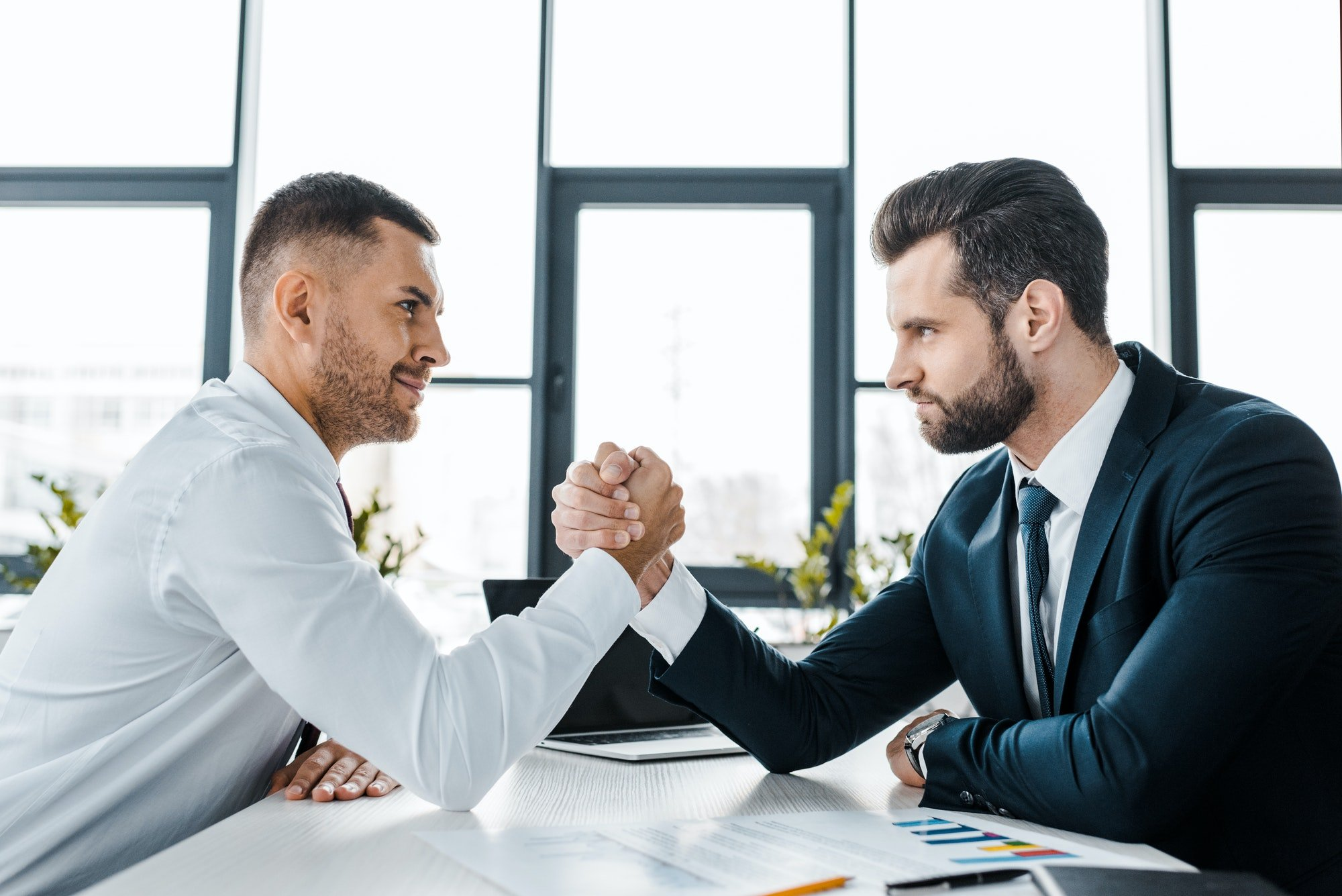 handsome businessmen competing arm wrestling in modern office